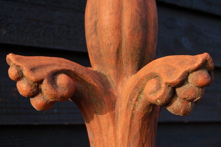 Fleur De Lys Roof Ridge Finial. 19th century copy. Cast in reconstituted stone, terracotta colour. Buy online or visit Debden Barns Antiques Saffron Walden.